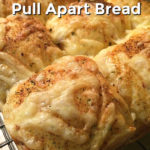 Cheesy garlic and herb pull apart bread rolls cooling on a black wire rack with a text overlay that says Cheesy Garlic & Herb Pull Apart Bread.