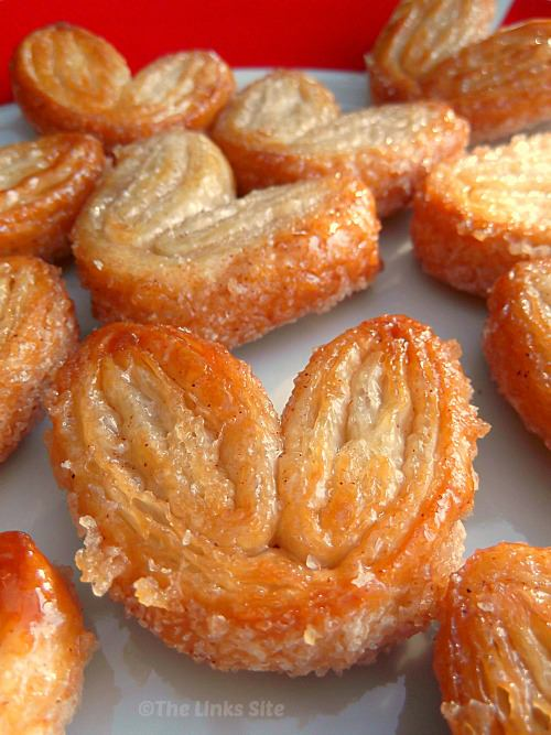 Batch of palmiers grouped together on a red and white plate.