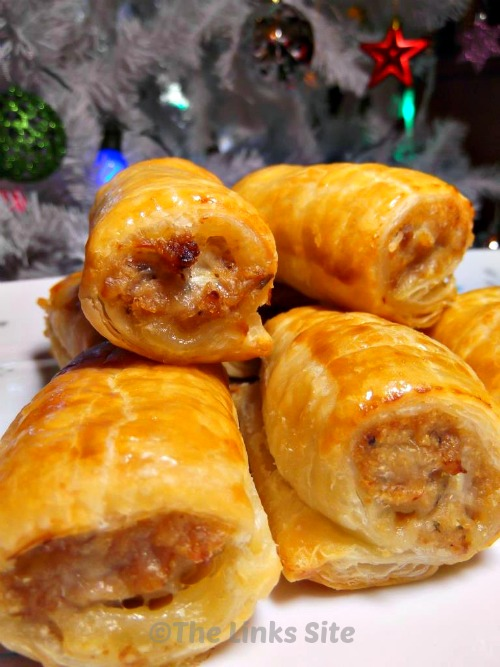 Group of sausage rolls on a plate with a Christmas tree in the background.