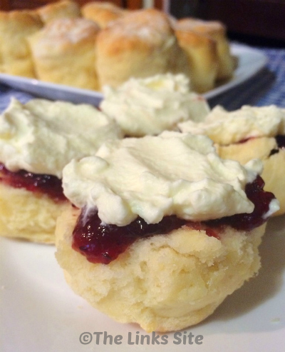 Scones topped with jam and cream on a white plate.