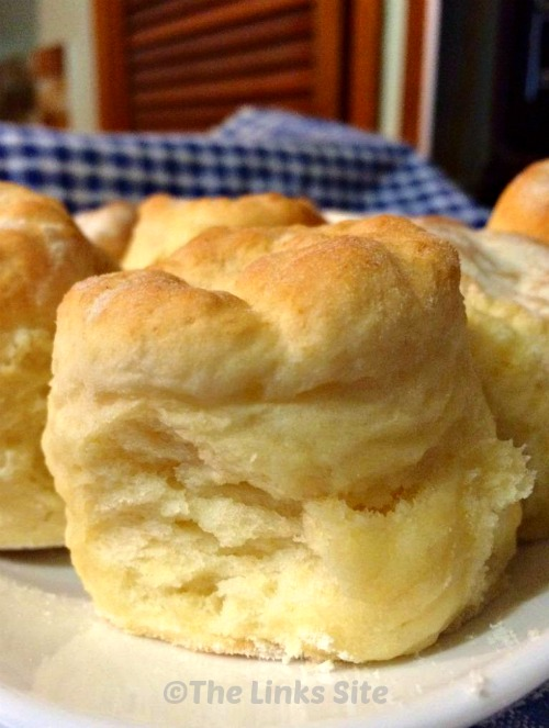 Close up of a batch of plain scones on a white plate.