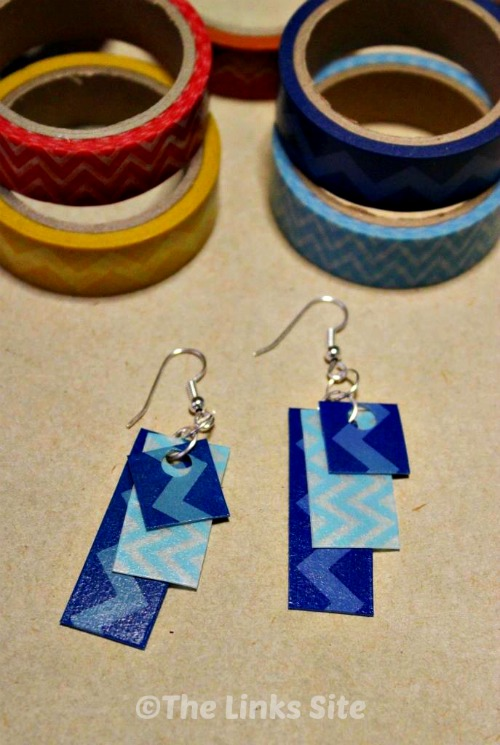 A pair of earrings is pictured lying on brown paper. They are decorated with zig zag washi tape in shades of blue. Rolls of washi tape can also be seen.