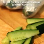 Thick cut strips of cucumber on a wooden chopping board. Whole cucumbers wrapped for storage can be seen in the background. Text overlay says: Simple Cucumber Storage Tips (great for when you have a large summer harvest!).