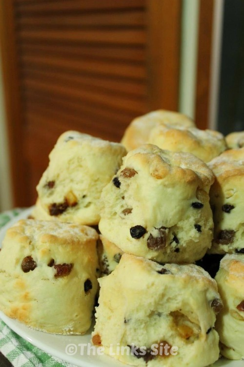 Batch of freshly baked fruit scones piled up on a plate.
