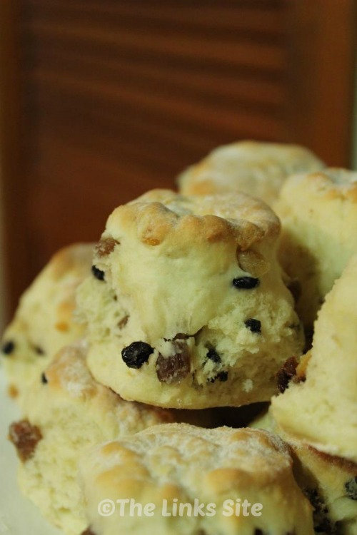 Close up of one fruit scone in a batch of fruit scones on a plate.