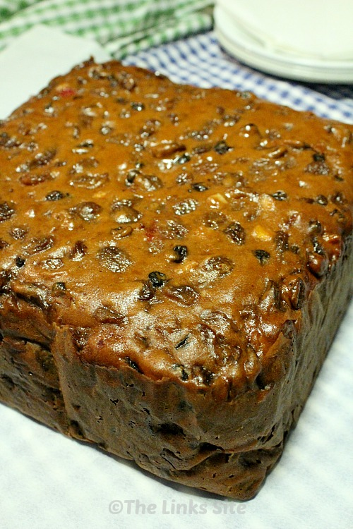 Square uncut fruit cake on a table with checked tea towels and white plates in the background.