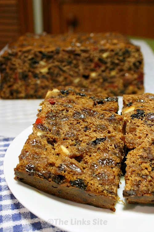 Slices of fruit cake on a plate with the remaining uncut cake in the background.