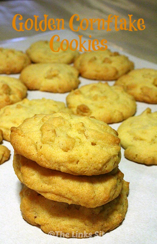 Stack of three cookies on baking paper, more cookies can be seen in the background. Text overlay says: Golden Cornflake Cookies.
