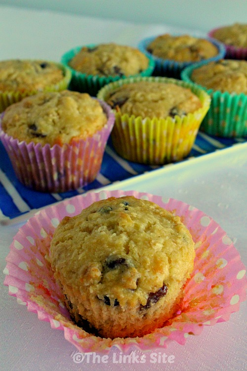 A single muffin is in the foreground with its paper case partially removed. More muffins can be seen in the background on a blue and white plate.