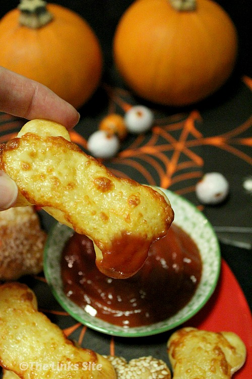 A cheese topped puff pastry snack has been dipped into the tomato sauce and is being held up for the camera. Halloween decorations such as pumpkins and eyeballs can be seen in the background.
