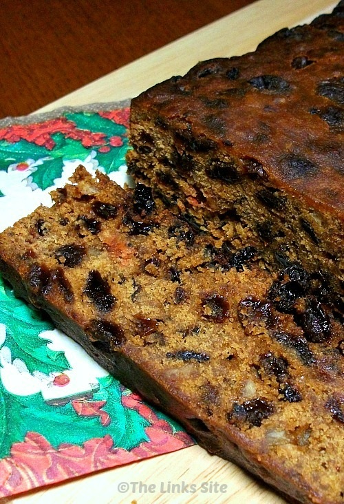 Traditional Christmas cake on a cutting board with a Christmas serviette. One slice of the cake has been cut off.