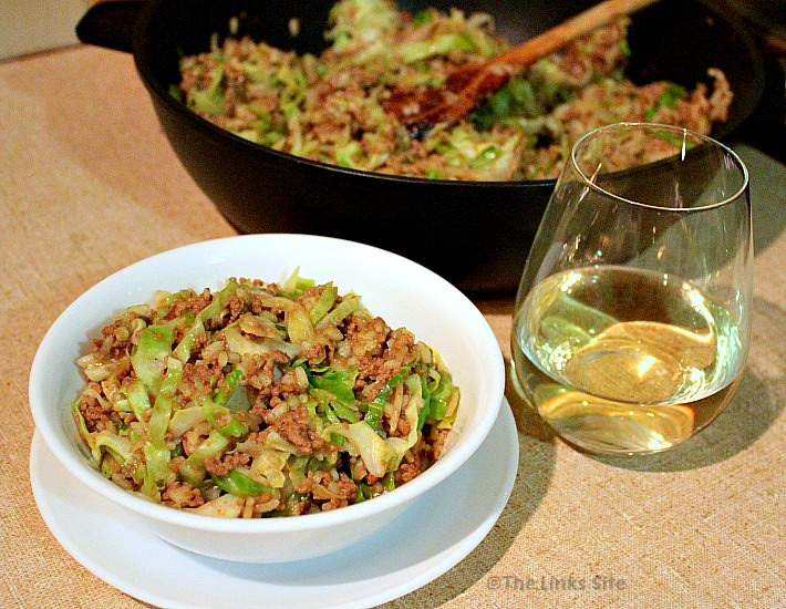 A glass of white wine is placed alongside a white bowl containing chow mein. A fry pan containing more chow mein and a wooden spoon can be seen in the background.