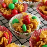 Honey Joys in Christmas themed paper cases on a wire cooling rack. Text overlay says: Crunchy Nut Honey Joys with M&M's!