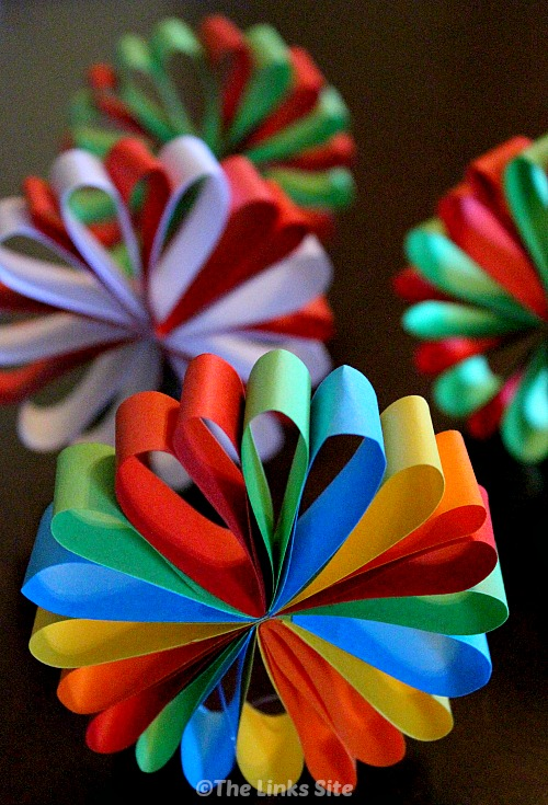 Four paper Christmas decorations on a wooden table.