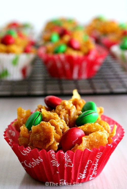 One honey joy topped with red and green M&M's in a red Christmas themed paper case. More honey joys can be seen in the background on a wire cooling rack.