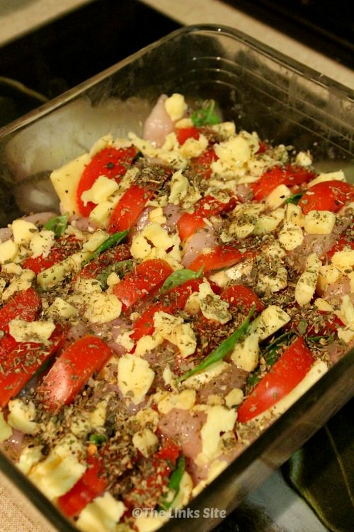 Raw chicken fillets in a glass baking dish. The fillets have been stuffed with tomato, basil, and cheese. Extra cheese and herbs are also sprinkled on top.