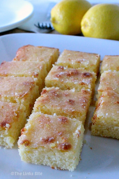 Squares of lemon cake on a white plate. Two lemons can be seen in the background.