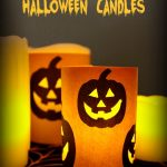 A dimly lit image showing battery powered pillar candles wrapped with orange craft paper that is decorated with Jack O Lantern faces. The facial features have been cut out so that the light from the candles shines through. Text overlay says: DIY Spooky Halloween Candles.
