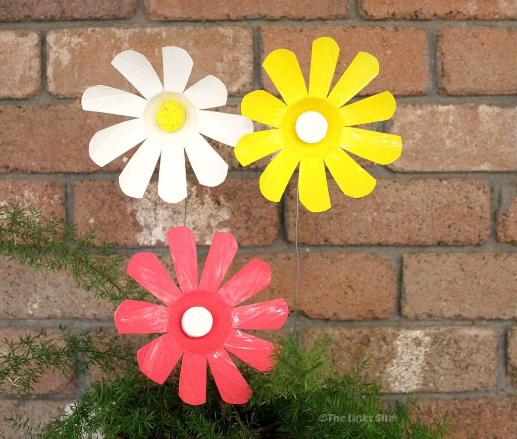 A pink, a white, and a yellow plastic bottle flower sticking up out of a plant pot via wires. A brick wall can be seen in the background.
