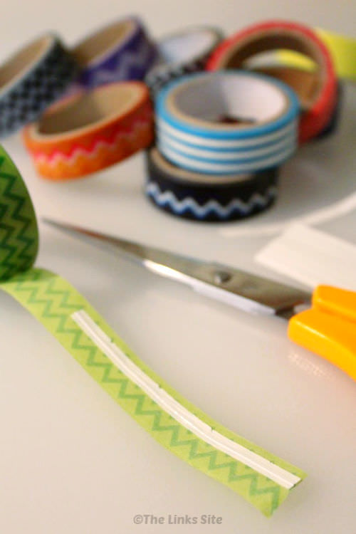 A white twist tie is placed on the sticky side of a piece of washi tape. Pair of scissors, more twist ties, and rolls of washi tape are seen in the background.