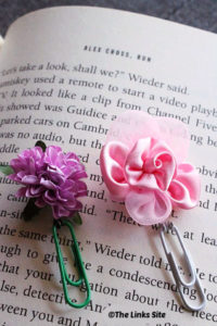 Two flower bookmarks resting on the page of a book. One has a green paperclip with a purple flower and the other has a white paperclip with a pink flower.