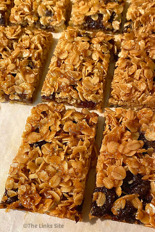 Several flapjacks are arranged in rows on a piece of baking paper.