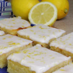 Iced lemon brownies on a blue plate. A blue and white patterned tea towel, two whole lemons, and a half of a lemon can be seen in the background.